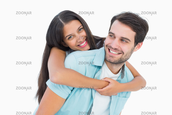 Happy casual man giving pretty girlfriend piggy back