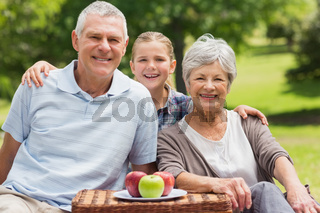 Smiling senior couple and granddaughter with picnic basket at park