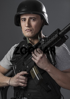 Fight, paintball sport player wearing protective helmet aiming pistol ,black armor and machine gun