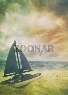 Toy sailboat in the sand with vintage look