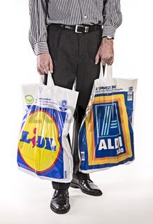 Mann mit Plastiktüten von Aldi und Lidl