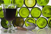 Rotweinglas vor Hintergrund mit leeren Flaschen