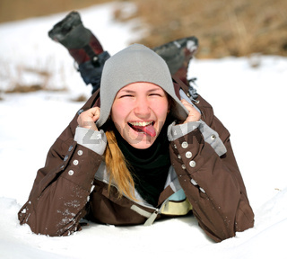 Close-up portrait of smiling young woman lying on a snow indicate the language and holding hands to her head. The concept photo winter recreation, healthy lifestyle , happy people