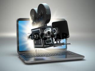 Video concept. Retro camera and  laptop.