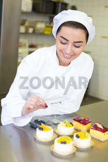 Confectioner preparing cakes at bakery or confectionery