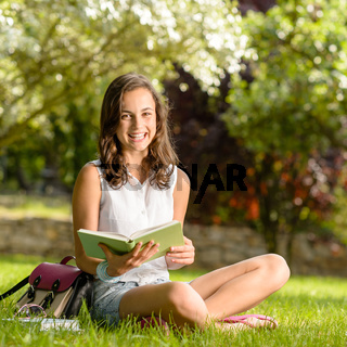 Cheerful girl with open book sitting grass