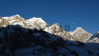 Rising moon over snow capped mountains
