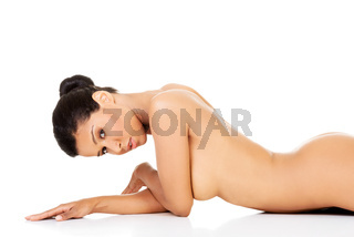 Attractive naked woman lying on the floor on her belly. Side view.