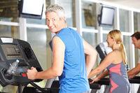 Senior auf Laufband im Fitnesscenter