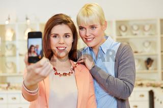 Frauen machen Selfie beim Shopping