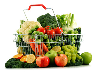 Shopping basket with assorted raw organic vegetables isolated on white