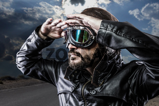 looking at the horizon biker with black leather jacket and old glasses