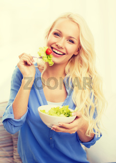 smiling young woman with green salad at home