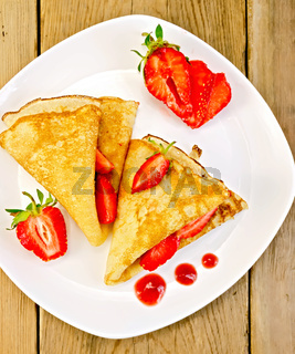 Pancakes with strawberries and jam on plate and board