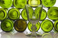 Weinglas vor leeren Weinflaschen