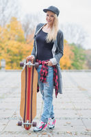 Gorgeous trendy blond woman with a skate board