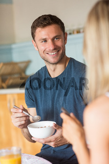 Cute couple having cereal for breakfast