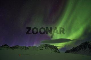 Nordlicht (Aurora borealis) ueber erleuchtetem Zelt, Kebnekaisefjaell, Lappland