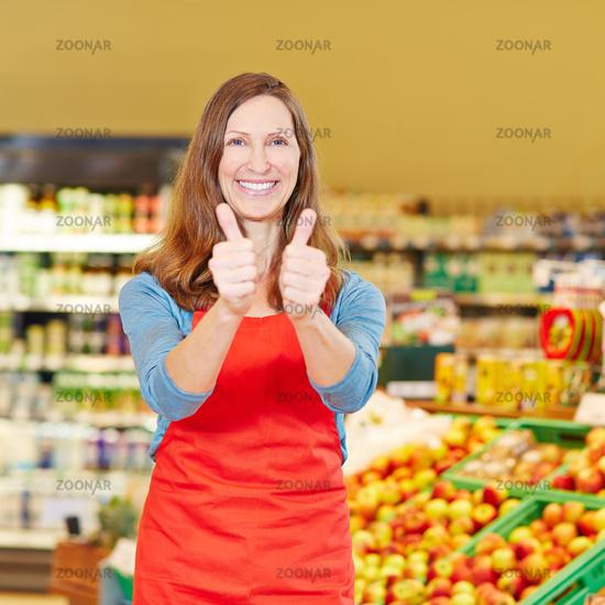 Lächelnde Marktleiterin hält Daumen hoch