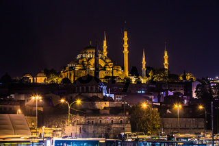 Night view on the restaurants at the end of the Galata bridge, Sultanahmet, at sunset with the famous Suleymaniye Mosque in the background, Istanbul,