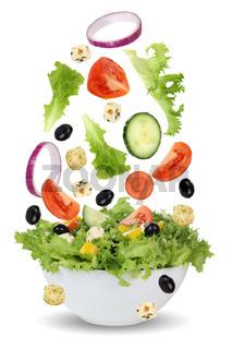Fallender Salat in Schüssel mit Tomate, Gurke, Zwiebel und Paprika