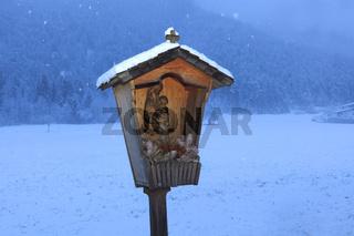 Wegkreuz im Schneefall