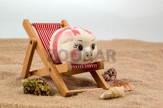 Liegestuhl mit Sparschwein