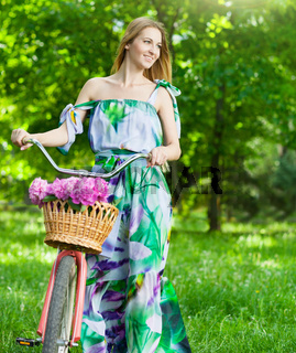 Beautiful blond woman wearing a nice dress having fun in park with bicycle carrying a beautiful basket full of peony flowers