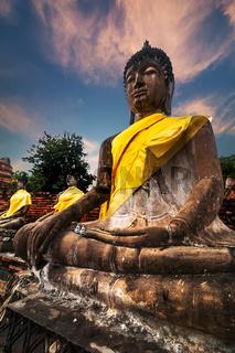 Ancient sculpture of meditating Buddhas at Wat Yai Chai Mongkhon temple sunset sky. Ayutthaya, Thailand