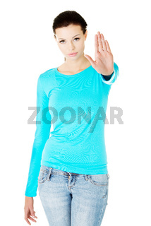 Beautiful casual woman showing stop gesture.