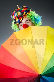 Funny clown with colourful umbrella