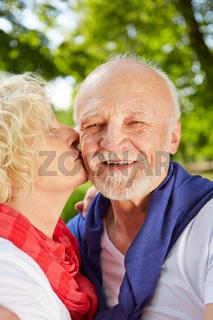 Frau küsst Mann auf die Wange im Garten