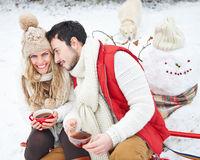 Paar mit Hund trinkt Tee im Winter