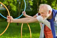 Senioren machen Sport mit Reifen im Garten