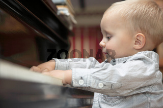 little boy playing piano indoor