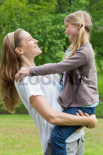 Smiling mother carrying daughter at park