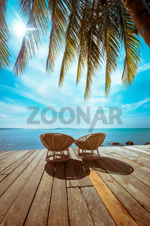 Tropical beach with palm tree and chairs