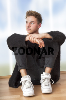 Casual dressed man sitting on the floor