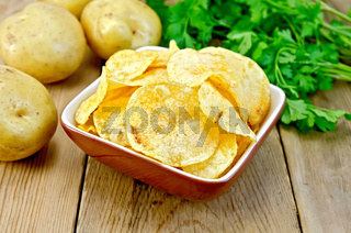 Chips in clay bowl with potatoes on board
