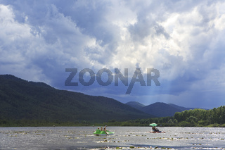 Sunrays breaking through storm clouds over mountain lake Manzherok.
