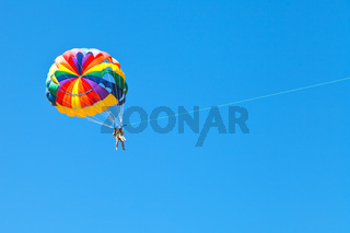 people parascending on parachute in blue sky