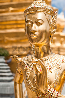 Golden Kinnari statue at Temple of Emerald Buddha (Wat Phra Kaew) in Grand Royal Palace. Half-bird, half-woman creature at south-east Asian Buddhist mythology. Bangkok, Thailand