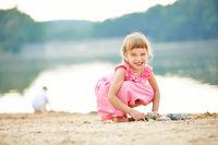 Mädchen spielt im Sommer am See
