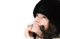 attractive smiling girl in warm fur hat on a white background
