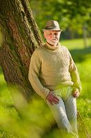 Senior lehnt an einen Baum im Herbst