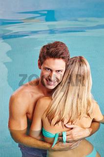 Mann umarmt Frau im Schwimmbad