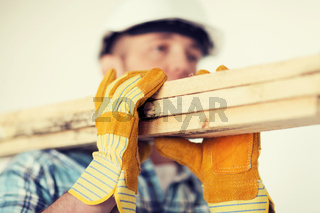 close up of male in gloves carrying wooden boards