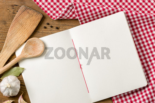 Book with wooden spoons on a red checkered tablecloth
