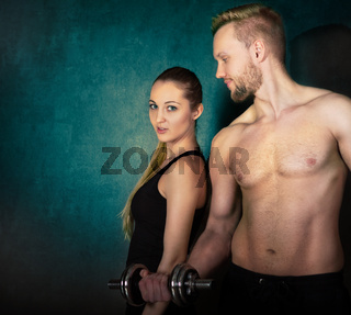 Athletic couple with a dumbells near the wall