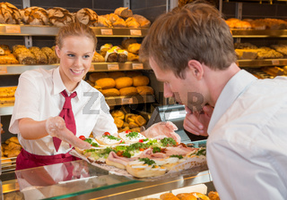 Shopkeeper in bakery showing sandwiches to customer